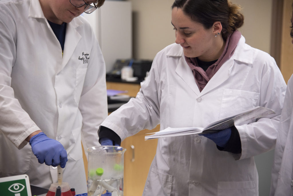 Male and female student in white lab coats observing samples