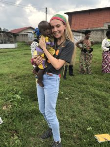 female student holding infant while on internship in Africa