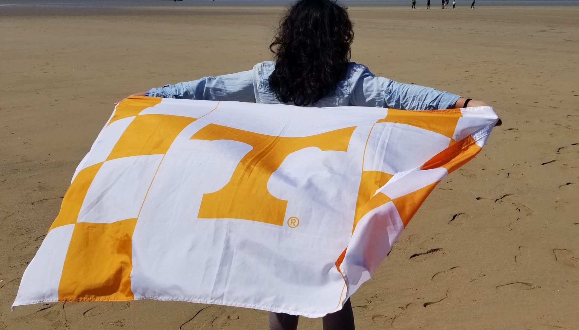 Female student with back to camera holding a University of Tennessee flag