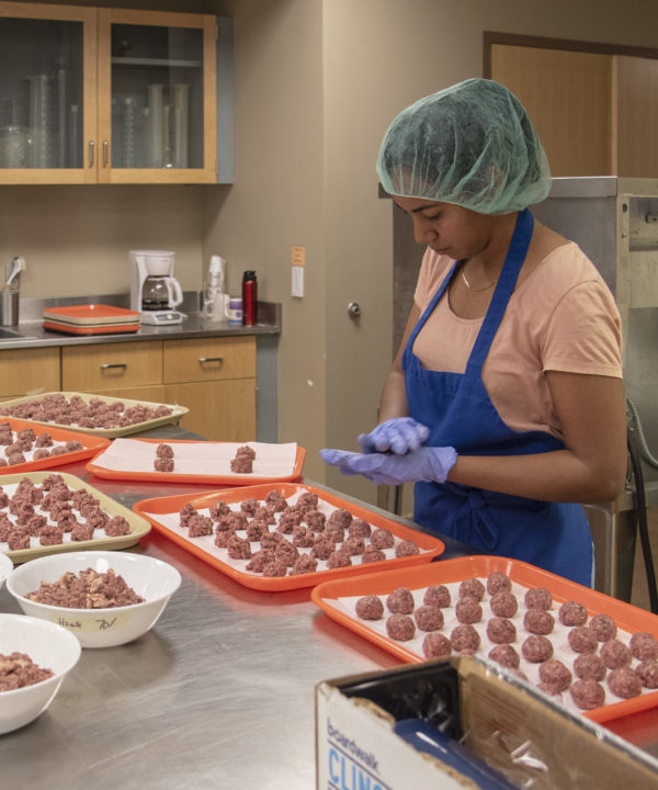 woman preparing meatball samples for sensory taste tests